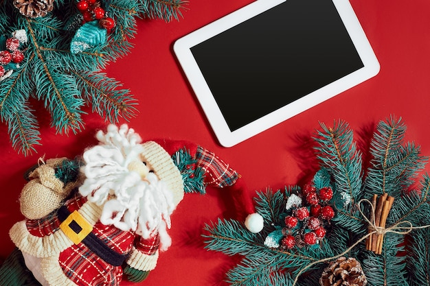 Рождественские украшения и белый планшет с черным экраном на ярко-красном фоне рождество и новый год ...