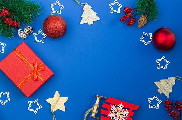 Елочные игрушки, шары, шишки, звезды, подарочные коробки и еловые ветки на синем фоне