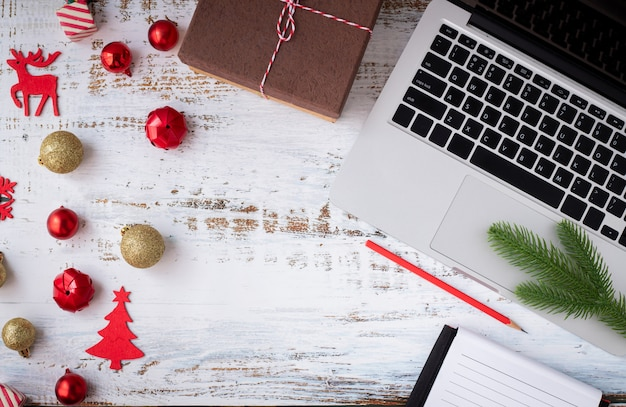 Christmas decorations, blank notebook paper and laptop, top view