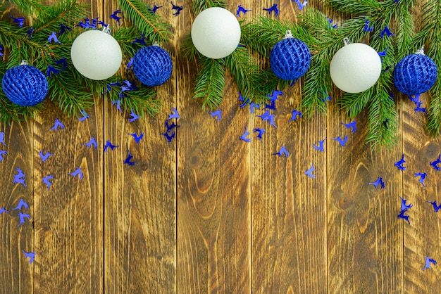 Christmas decorations, blue and white balls on a brown wooden table. top view, copy space.