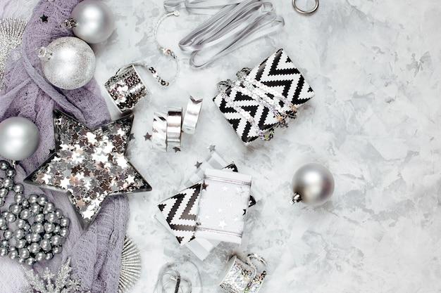 Рождественские украшения, банты, звезды в серебряном цвете на сером фоне. праздник и торжество. плоская планировка, вид сверху