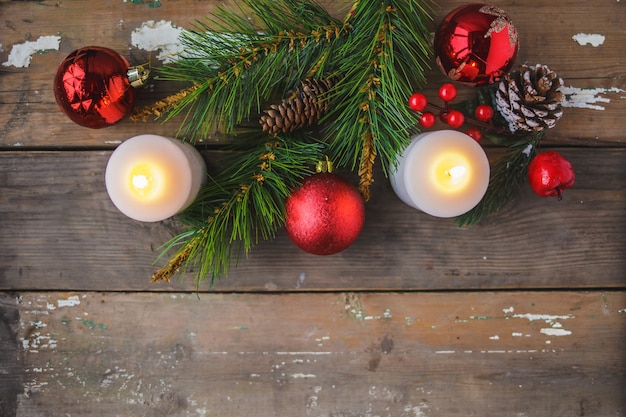 Christmas decorations, burning candles, spruce on a wooden background. new year's . postcard