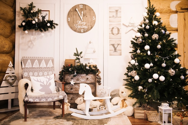 Christmas decorations: chair, christmas tree, chest of drawers, clock, gifts on the background of a wooden wall. christmas photo zone. christmas photo zone with a christmas tree.
