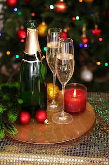 Christmas decorations and champagne bottle and glasses on bright background