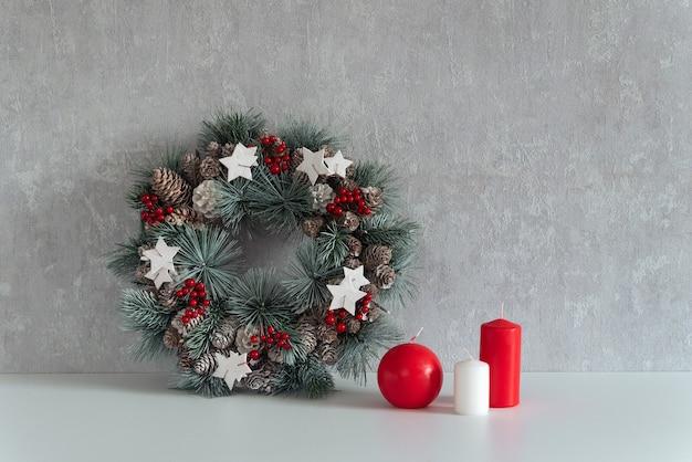 クリスマスの装飾:灰色の背景にクリスマスリースとキャンドル。居心地の良いインテリア。
