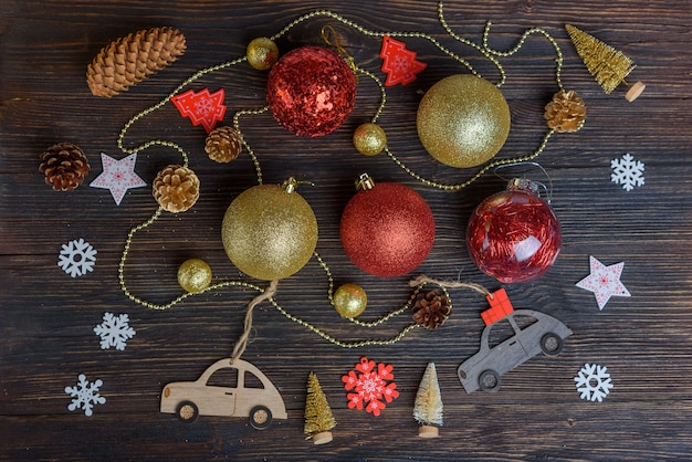 Christmas decorations, cones and children's cars on a dark wooden