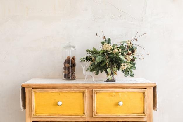Christmas decorations and conifer twigs placed on dresser with yellow drawers on white wal