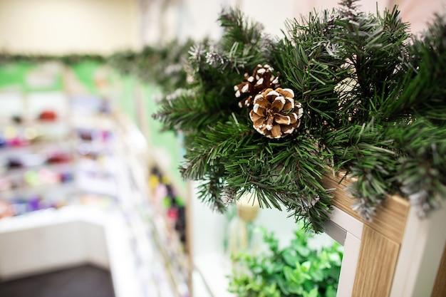 Рождественские украшения хвойных ветвей с шишкой в косметическом магазине. размытые полки с продуктами по уходу за кожей и волосами в косметическом магазине в качестве фона.