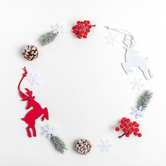 Christmas decorations deer, fir twigs, red berries, snowflakes laid out in circle on white backdrop