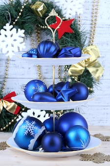 Christmas decorations on dessert stand, on  color wooden background