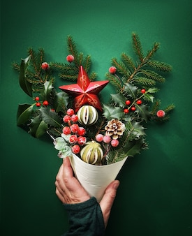 Christmas decorations, fir twigs, berries, holly, dry lime and star in cone held in hand, flat lay
