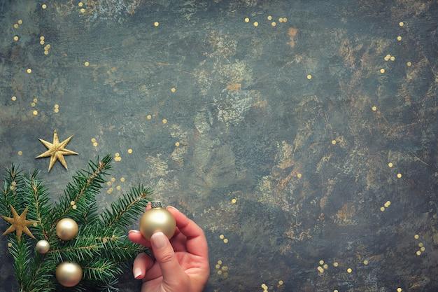 金色のおもちゃで飾られたモミの小枝を両手でフラットに置くクリスマスの装飾。暗いテクスチャテーブルの上からフラット横たわっていた、トップビュー。