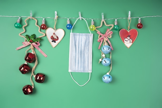 Decorazioni natalizie in una ghirlanda di luci colorate e mascherina medica. concetto di pandemia