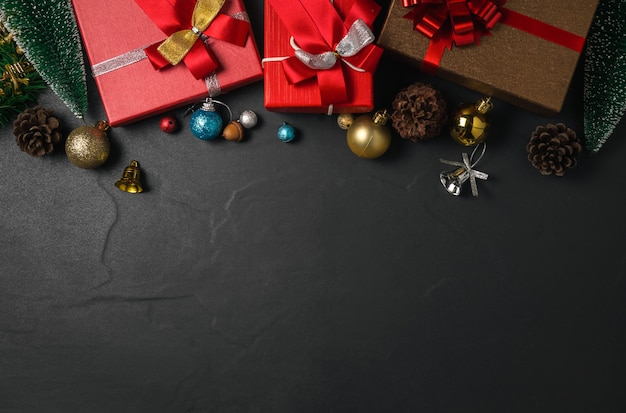Christmas decorations and gift box on dark table. top view with copy space and xmas greeting card. happy new year concept.
