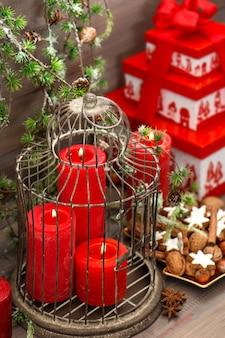 クリスマスの飾り、ギフトボックス、赤いろうそく、クッキー、ナッツ、木製の背景の断片。松の枝とヴィンテージスタイルの家のインテリア