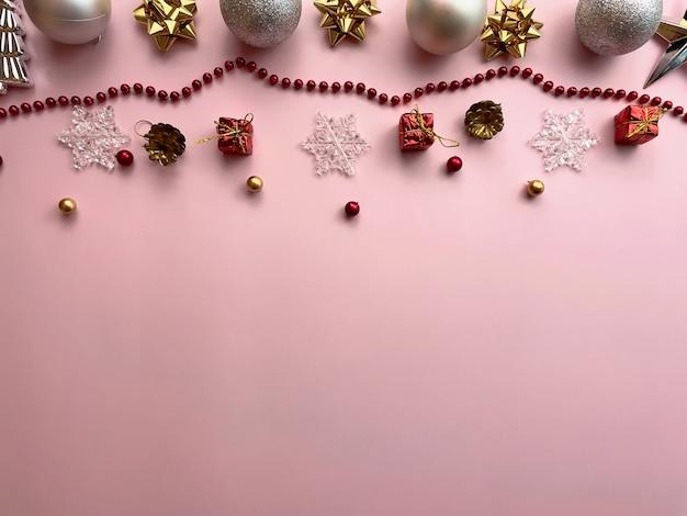 クリスマスの飾り、ギフトボックスのリボン、金色のボール、雪片、ピンクの背景に赤いボール