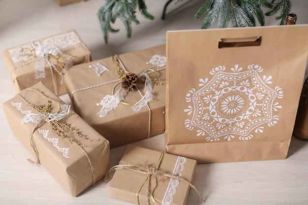 Подарочные коробки рождественских украшений в упаковочной бумаге около рождественской елки.