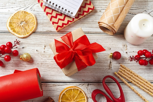 Christmas decorations and gift wrapping items on wooden , copyspace