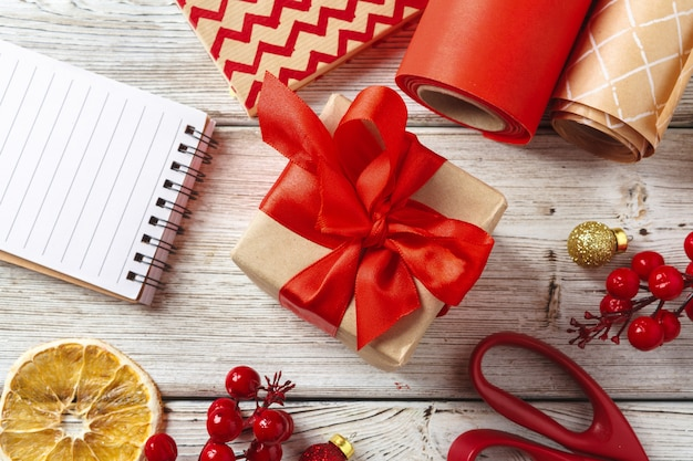 Christmas decorations and gift wrapping items on wooden surface, copy space