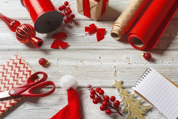 Christmas decorations and gift wrapping items on wooden surface