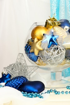 Christmas decorations in glass vase on fabric background Premium Photo