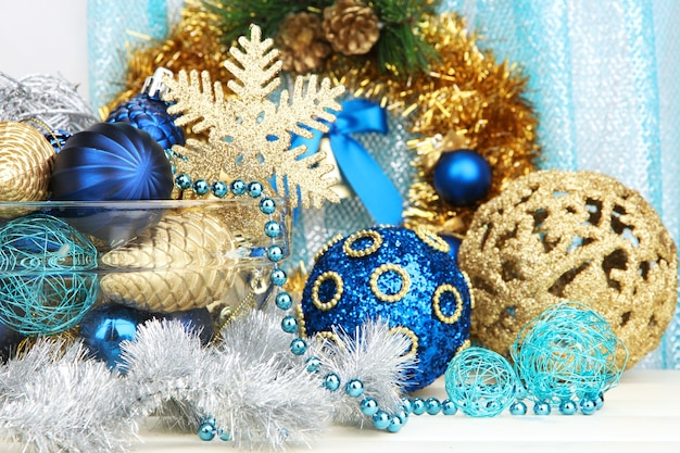 Christmas decorations in glass vase on fabric background