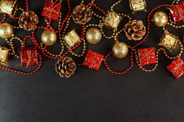 Christmas decorations in gold and red on a black background with free space. view from above. christmas mood.