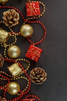 Christmas decorations in gold and red on a black background with free space.