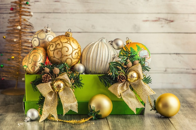 Christmas decorations in green box on light wood