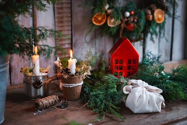 크리스마스 장식 수제 양초. 손으로 만든 섬유 크리스마스 트리를 직접 손으로 축제 테이블. 저렴한 새해. 프리미엄 사진