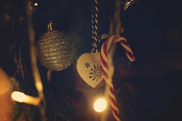 クリスマスの飾りは、輝く花輪に囲まれた枝に掛かっています。