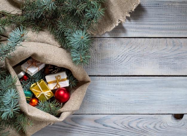 Рождественские украшения в мешке на белой деревянной поверхности. вверх vi