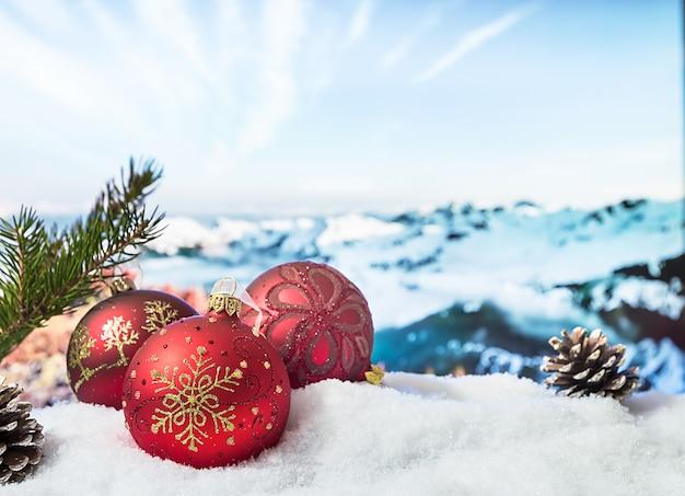 눈 덮인 산 앞 눈 더미에 크리스마스 장식. 겨울 크리스마스 배경입니다.