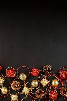 空きスペースのある黒の背景にゴールドと赤のクリスマスデコレーション。上からの眺め。クリスマスムード。