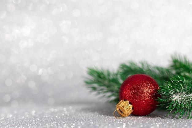 ぼやけたキラキラ背景、コピースペースに木の枝と赤いボールで作られたクリスマスの装飾