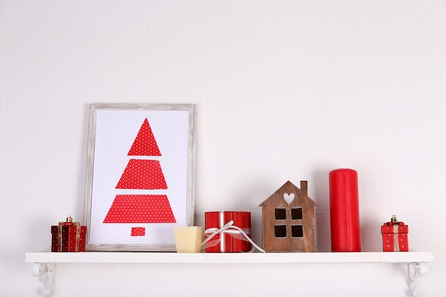 Christmas decorations on mantelpiece on white wall