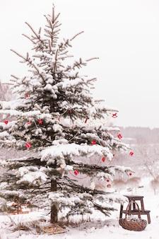 Елочные игрушки на красивой елке, засыпанной снегом