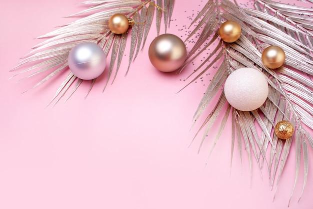 Елочные игрушки на розовом фоне декоративные золотые пальмовые листья елочные шары
