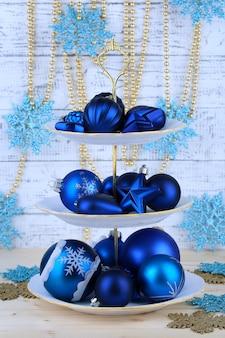 カラーの木製の背景に、デザートスタンドのクリスマスデコレーション