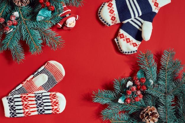 真っ赤な背景のクリスマスの装飾。クリスマスと新年のテーマ。あなたのテキスト、願い、ロゴのための場所。モックアップ。上面図。スペースをコピーします。静物。フラットレイ。