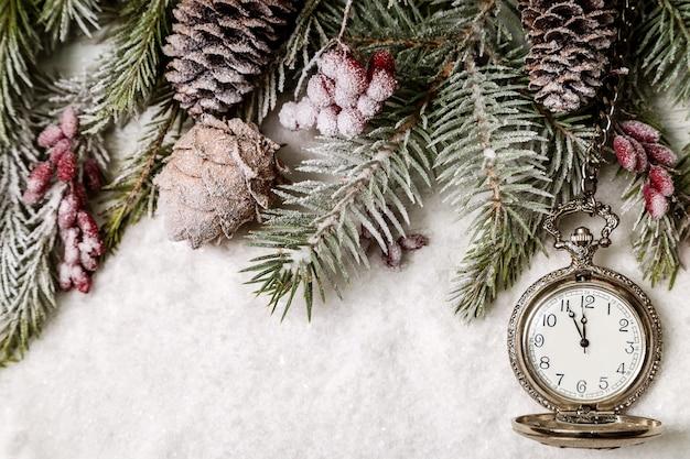 時計と雪の上のクリスマスの装飾