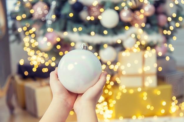 子供の手に木の上のクリスマスの飾り。セレクティブフォーカス。ホリデー。