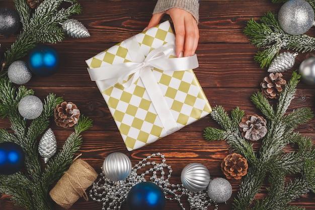 Рождественские украшения на деревянном столе с украшенным подарком в руках женщины