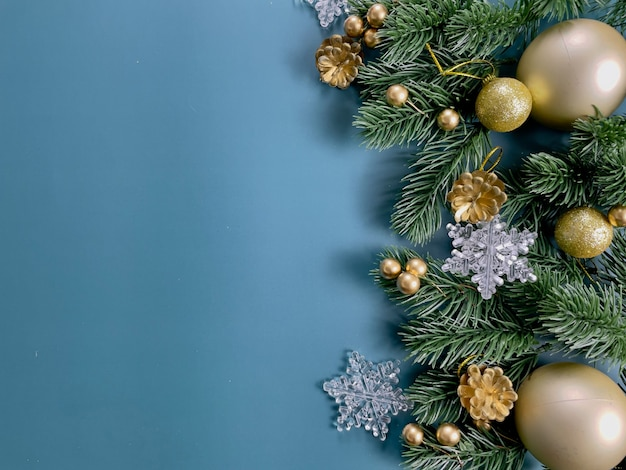 クリスマスの装飾、松の葉、金色のボール、雪片、青い背景の上の金色の果実