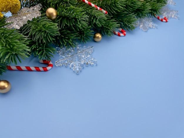 クリスマスの装飾松の木は青い背景に金色のボールの雪片を残します
