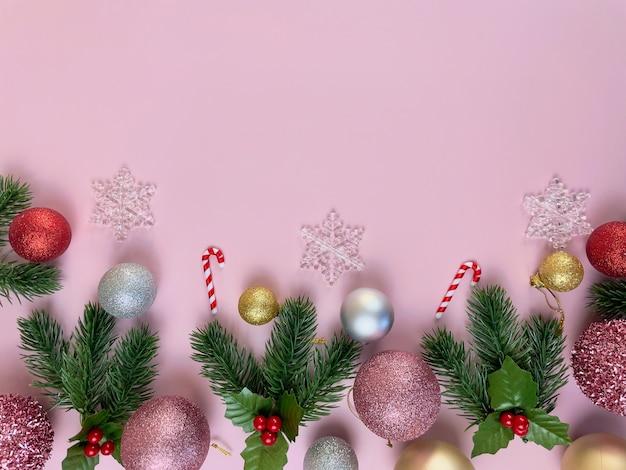クリスマスの装飾、松の葉、金色のボール、雪片、ピンクの背景に赤いボール