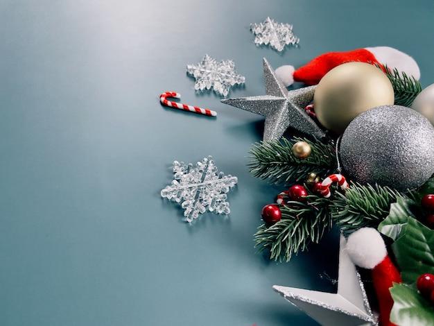 クリスマスの装飾松の木は青い背景に金色のボール雪片赤いベリーを残します