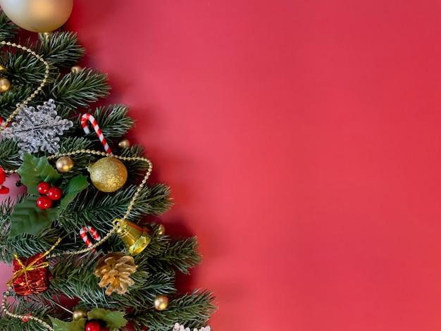クリスマスの装飾松の木は赤い背景に金色のボール雪片赤いベリーを残します
