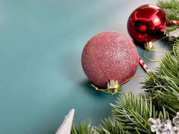 クリスマスの装飾、松の葉、赤いボール、雪片、青い背景の上の赤いベリー