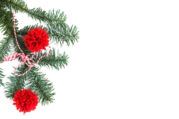 Christmas decorations: red pompons and christmas tree branch on white